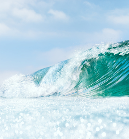 ocean wave: A breaking ocean wave with bright bokeh patterns in the foreground.  A somewhat slow shutterspeed was used for a partial blurring effect. Stock Photo