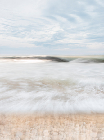 desaturated colors: An abstract seascape with blurred panning motion combined with a long exposure.  Image displays soft, desaturated colors.