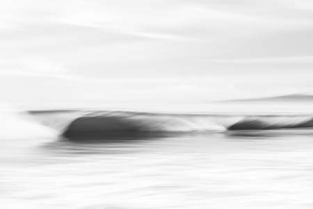 seascape: An abstract, black and white seascape featuring crashing ocean waves.  Image made with panning motion and a long exposure for a soft, blurred effect. Stock Photo