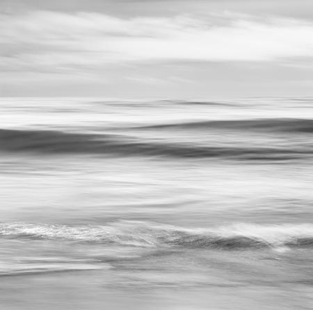 Een abstract, zwart en wit zeegezicht featuring convergerende oceaangolven. Afbeelding gemaakt met panning beweging en een lange blootstelling voor een zachte, wazig effect.