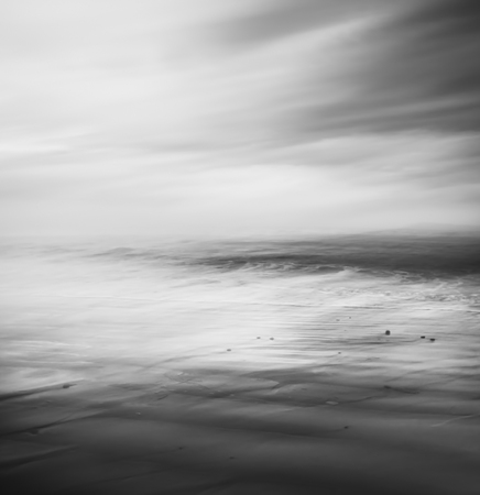 abstract black: An abstract seascape rendered in black and white.  Image made using a long exposure and panning movement for a soft, blurred effect. Stock Photo