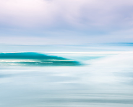 A breaking ocean wave with a moody sky. Image made with a long exposure for a soft blurring effect.