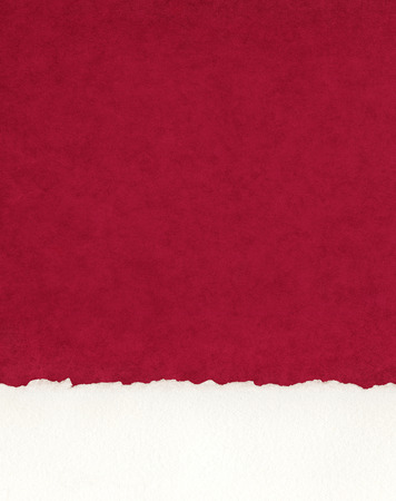 deckled: A section of deckled edge paper on a textured red background.