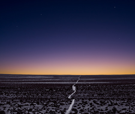 A lonely and empty Mojave desert road just after sunset. Stock Photo
