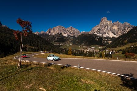Oct. 2018, Alta Batia, Hochabteital, Dolomiten, Suedtirol, Italien, Classic car oldtimer in autumn on a pass road with blue sky