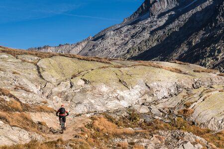 Grimselpass, Valais canton, Bernese Oberland, Switzerland, Oct. 2018, Cyclists at the summit, cantonal border, view of the Valais Alps, Valais canton, Bernese Oberland, Switzerland
