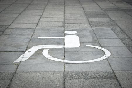 White painted disabled parking sign on black road surface. photo