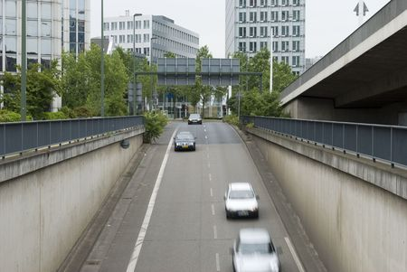 Vehicles drive into the tunnel under the Bridge at day time.  photo