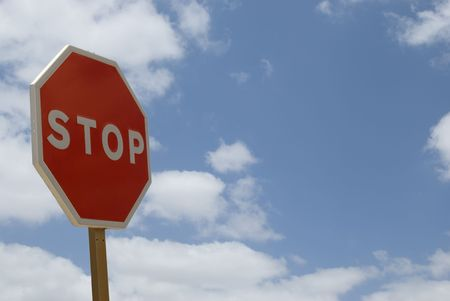 Stop traffic sign against blue cloudy sky. Stock Photo