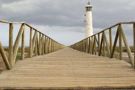 Lighthouse with  wooden footbridge at the beach of Jandia. Fuerteventura. Spain