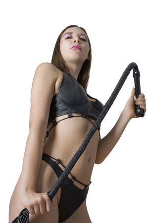 Woman in sexual dominatrix black leather lingerie and with a whip in her hand. Studio shot. Isolated on white background. Stock Photo