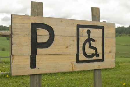 parking violation: Wooden Handicapped Parking Only sign. Permit Parking sign For disabled person.