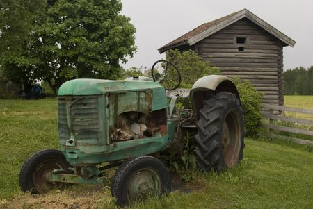 Old abandoned rusty tractor in front of Old farmer's wooden house museum Gamle Hvam. Norway.  Stock Photo - 7140182