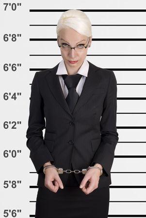 mug shot: Mug shot of young business woman locked in handcuffs.
