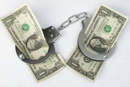 Close-up handcuffs and money over white background. Not isolated. Stock Photo - 7972614