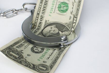 Close-up handcuffs and money over white background. Not isolated. photo