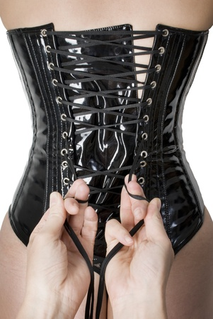 dominatrix: Male hands tightening up a corset to the young sexy woman.