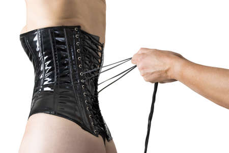 Male hands tightening up a corset to the young sexy woman. photo