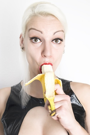 Beautiful sexy young woman eating banana. Not isolated. photo