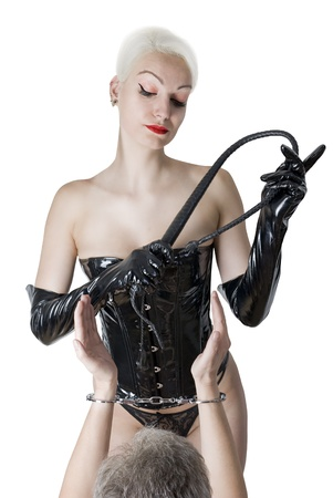 Young Woman in sexual dominatrix black leather lingerie with a whip in her hand. Dominating a slave. Studio shot. Isolated on white background. photo