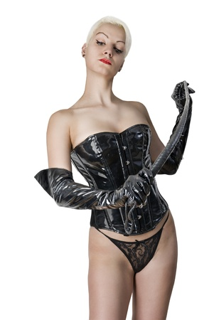 Young Woman in sexual dominatrix black leather lingerie with a whip in her hand. Studio shot. Isolated on white background. Stock Photo