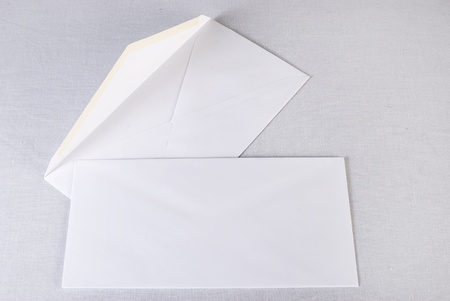 Close up of a two white envelopes on white background. Not isolated.