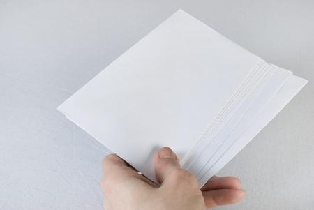 Mano femenina que sostiene un sobres sobre fondo blanco. No aislado