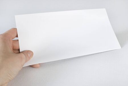 Female hand holding an envelope over white background. Not isolated. Stock Photo