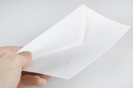 Female hand holding an envelope over white background. Not isolated. photo