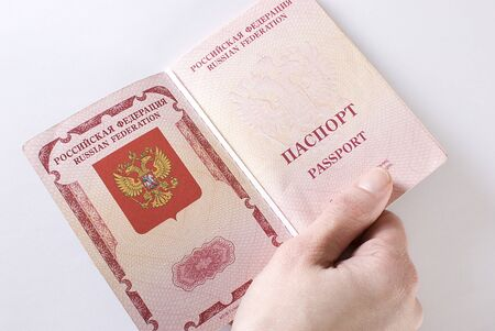 Russian international traveling passport in female hand over white background. Not isolated.