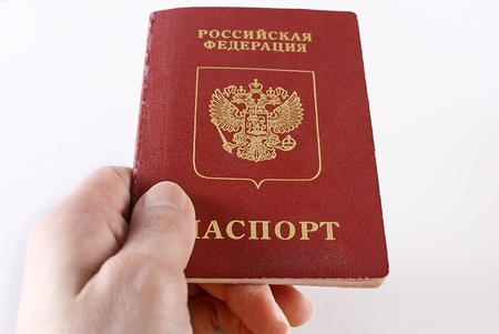 Russian international traveling passport in female hand over white background. Not isolated. Stock Photo