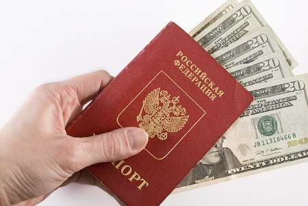 Russian international traveling passport and money in hand over white background. Not isolated.