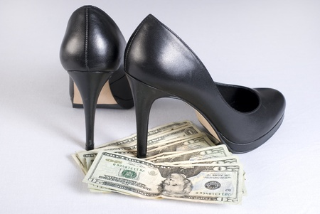 High heel shoes on money over white background