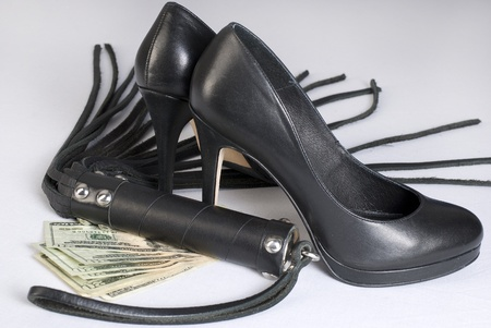 Strict Black Leather Flogging Whip, high heels shoes and money on white background. Not isolated. photo