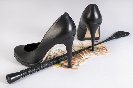 herrin: Leather Short Handle Crop, High Heels und Geld auf weißem Hintergrund. Nicht isoliert.