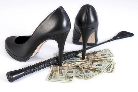 Strict Black Leather Flogging Whip, High Heels Schuhe und Geld auf weißem Hintergrund. Nicht isoliert.
