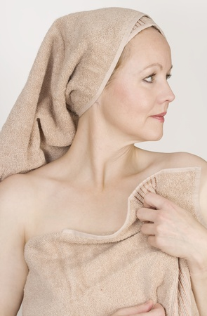 Adult beautiful woman after bath with a towel on her head. Over white. Not isolated.