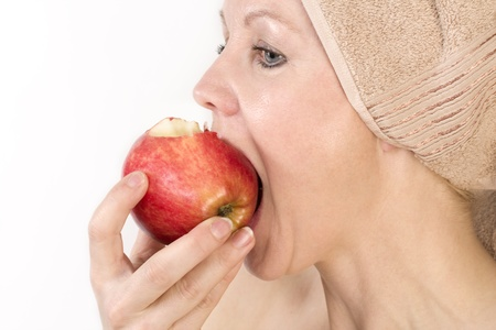 Adult woman with a towel on her head biting an apple. Over white. Not isolated.