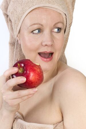 Adult woman with a towel on her head biting an apple. Over white. Not isolated.  photo
