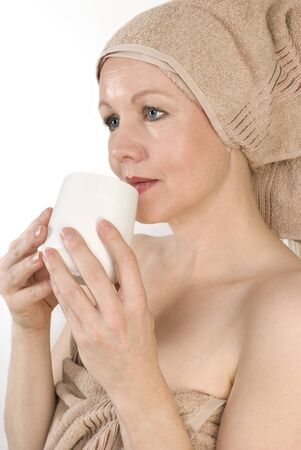 Adult beautiful woman after bath with a towel on her head. Over white. Not isolated. photo
