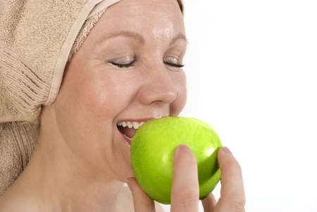 Adult woman with a towel on her head biting an apple. Over white. Not isolated. Stock Photo