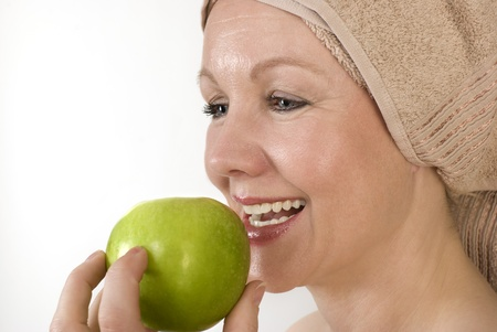 Adult woman with a towel on her head biting an apple. Over white. Not isolated. Stock Photo - 11762771