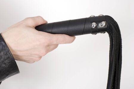 Látigo de cuero Negro Flogging en mano femenina. Sobre blanco, No isilated. Foto de archivo
