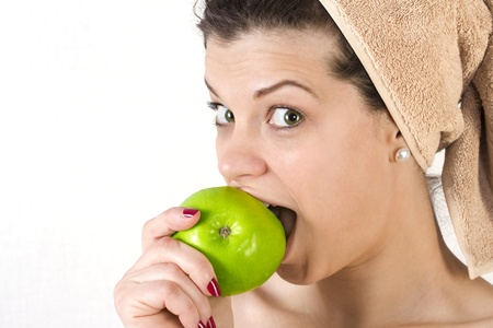 Beautiful young woman after bath with a towel on her head and an apple in her hand. Over white. Not isolated. Stock Photo