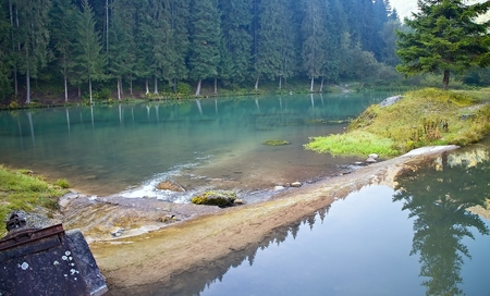 ruzomberok: Ruzomberok - Cutkovska valley - rocks in a water reservoir with mirroring trees on the water surface. Water, trees and mirror Stock Photo