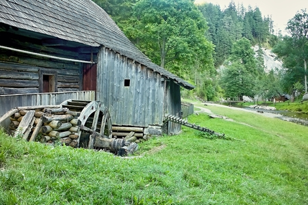 Mlyny - Oblazy - an old wooden water mill in the Kvacany valley. Wooden milling wheel, grass, mountain river and forest.