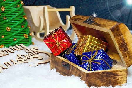 Christmas greetings for Christmas time. Snowflakes covered with evening sky with Santa Claus sleigh, Christmas tree and chest full of expected gifts. Merry Christmas wooden inscription. Stockfoto