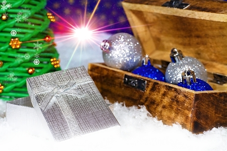 Open box with Christmas present under Christmas tree. Stock Photo