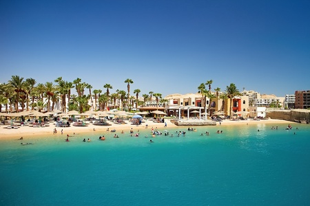 Beach at the Red Sea in Egyptian Hurghada. Palm trees, sand, Red sea and beautiful summer sunny day.