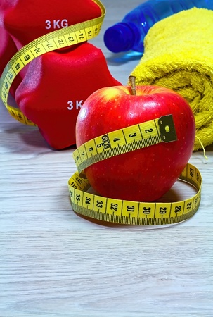 Red apple with measure tape on board.